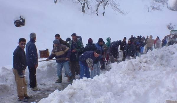 Les jeunes Kabyles dégagent la route bloquée par la neige.