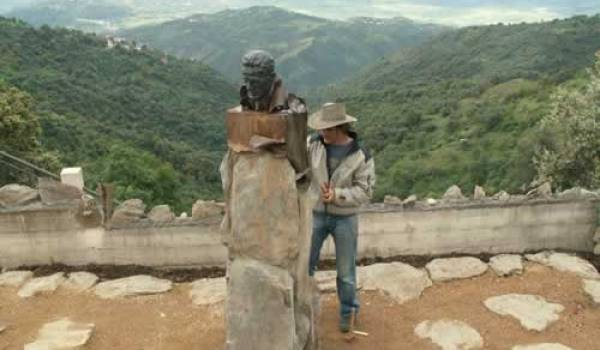 Le sculpteur Olivier Graïne à côté du buste de Mouloud Mammeri en Kabylie.