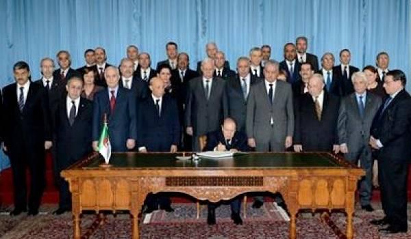 Le président signant la loi de finances entouré du gouvernement.
