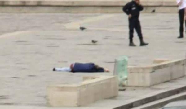 Farid Ikken au sol à côté de policiers qu'il a agressé avec un marteau.